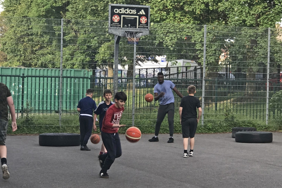 Daniel Edozie playing basketball with young people at Empire Fighting Chance in Easton, Bristol