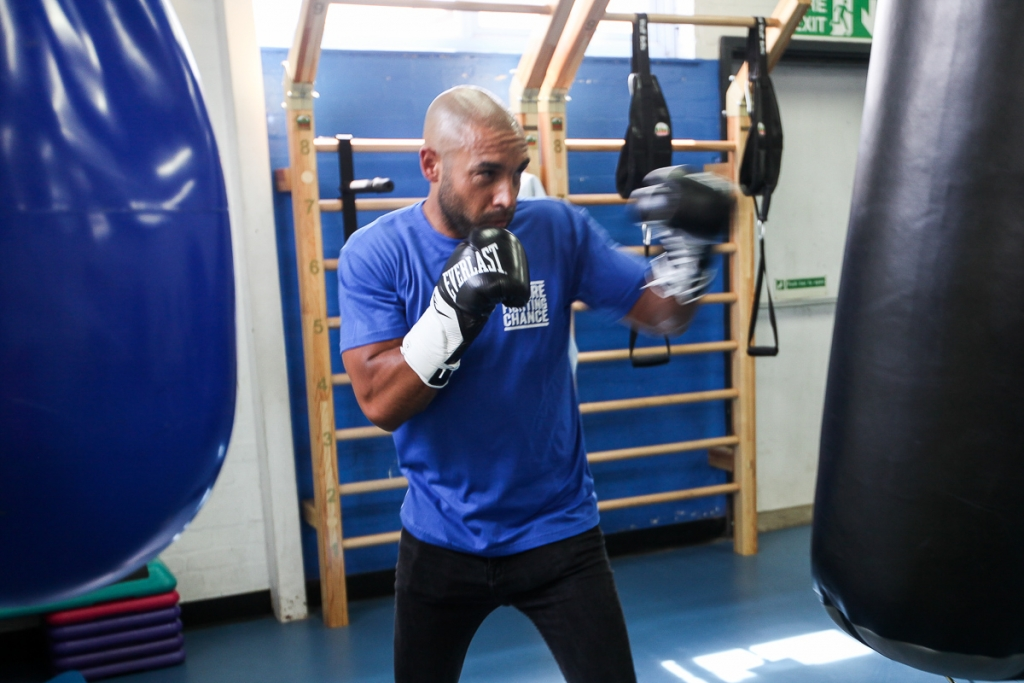 Alex Beresford at Empire Fighting Chance boxing gym, wearing Empire Fighting Chance t-shirt, hitting punch bags as part of photoshoot for his Empire Fighting Chance ambassadorship announcement.