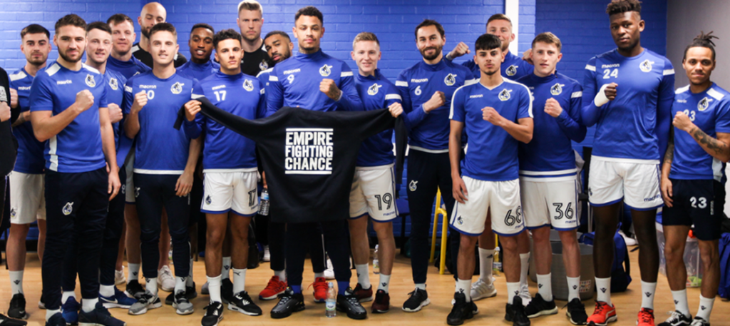 Bristol Rovers squad lines up for team photo with Empire Fighting Chance jumper